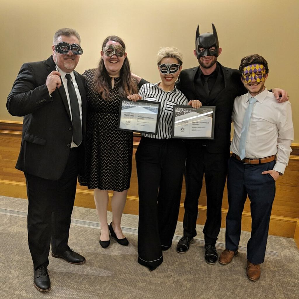 The whole WSS team stands, smiling, wearing masquerade masks and holding two awards.