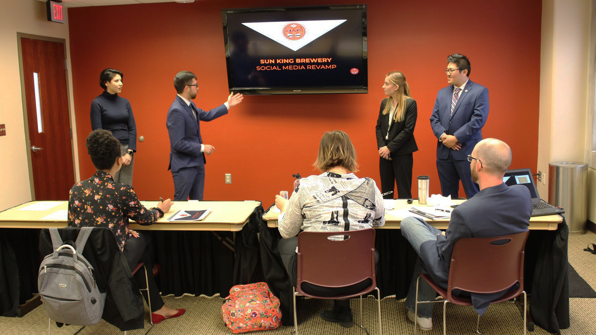 "Four students stand at the front of the room, on either side of a tv which reads ""Sun King Brewery Social Media Revamp"". Three judges sit at a table watching this presentation."