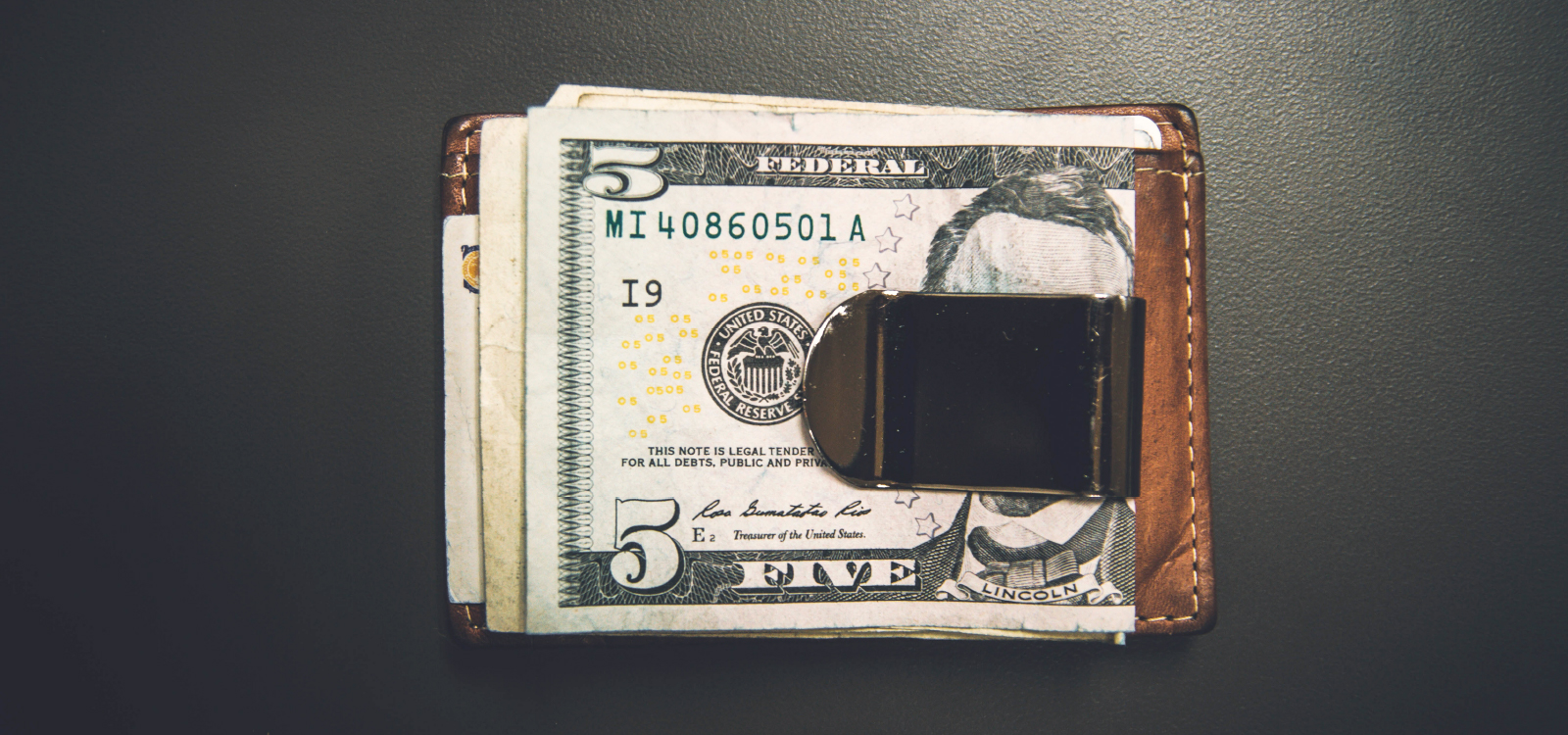 A money clip with five dollars on top.